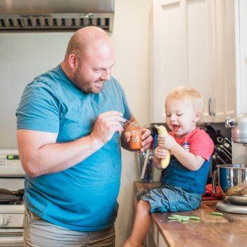 Dad feeding baby vegetables